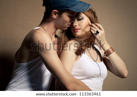 portrait of a beautiful casual couple in jeans sitting together over wooden background. boy hugging girl and kissing. studio shot