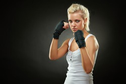 Portrait of a beautiful caucasian boxer girl with black bandage on hands, studio shot