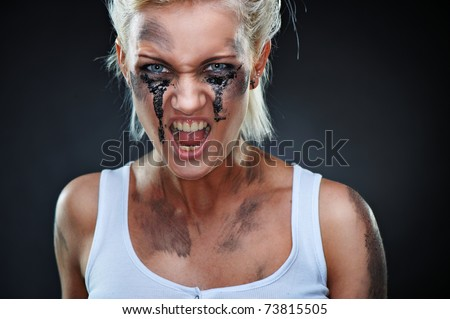 Portrait of a beautiful caucasian punk girl with dirt on her face. Shouting, studio shot