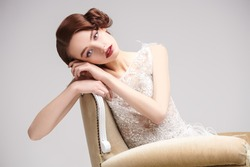 Portrait of a beautiful chic woman posing in a luxury white dress in vintage armchair. Evening makeup and hairstyle of the 20s.