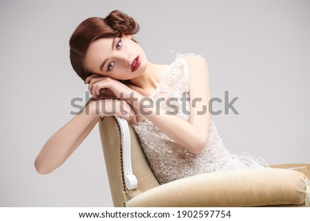 Portrait of a beautiful chic woman posing in a luxury white dress in vintage armchair. Evening makeup and hairstyle of the 20s.  Stock fotó ©
