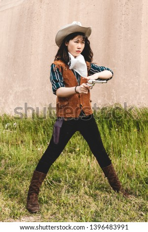 Portrait of a beautiful Chinese female cowgirl shooting with a gun in the wild west in front of a wall
