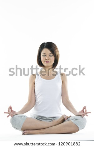 Portrait of a beautiful Chinese woman in Lotus yoga position with eyes closed.