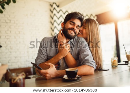 Portrait of a beautiful couple while having romantic moments in cafe. Girl hugging her handsome boyfriend. #1014906388
