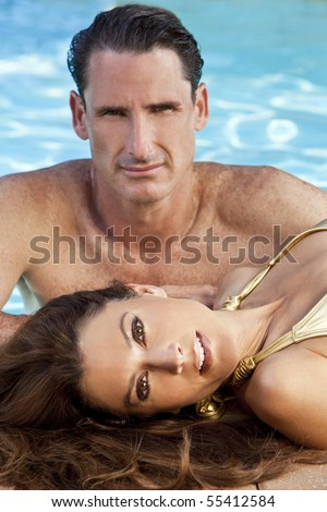 Portrait of a beautiful couple with a woman laying down at the side of a swimming pool with an attractive man behind her. The focus is on the woman in the foreground.