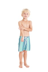 Portrait of a beautiful curly blond European boy wearing swimming shorts. Studio shot, isolated on white background.