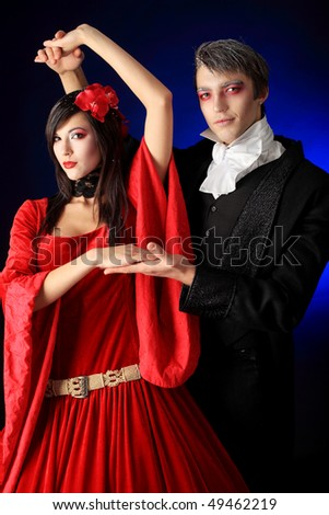 Portrait of a beautiful dancing couple in medieval costumes with vampire style make-up. Shot in a studio.