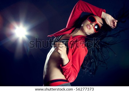 Portrait of a beautiful dancing girl on dark background