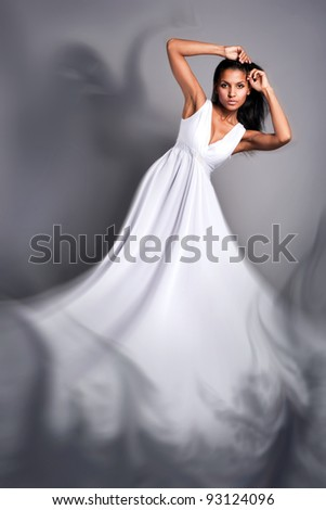 portrait of a beautiful dark-skinned woman in a white dress in the studio