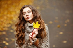 Portrait of a beautiful, dreamy and sad girl with long wavy hair in knit sweater autumn