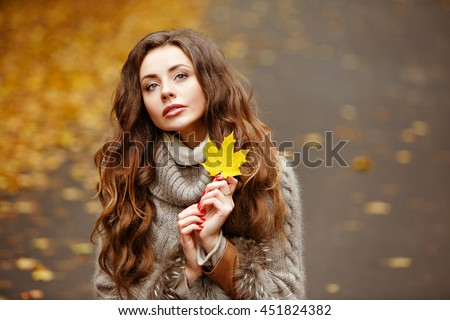 Portrait of a beautiful, dreamy and sad girl with long wavy hair in knit sweater autumn #451824382