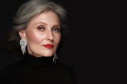 Portrait of a beautiful elderly woman in a white shirt with classic makeup and gray hair