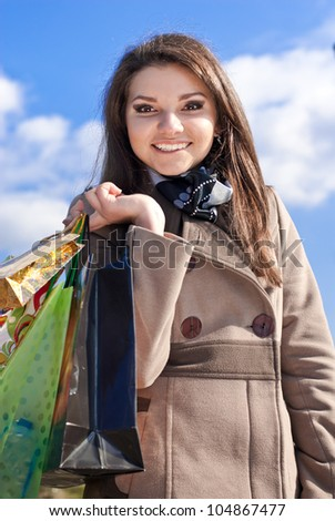 Portrait of a beautiful Elegant Happy smiling young woman carrying some shopping bags on a bright sunny day of spring, autumn or winter with blue sky on the background