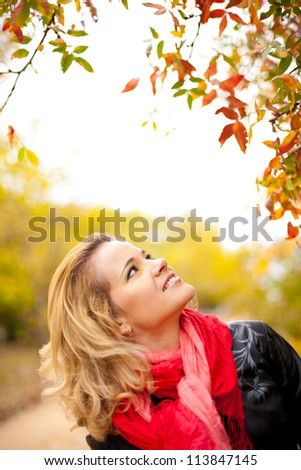 Portrait of a beautiful elegant woman posing while standing in a park in autumn.