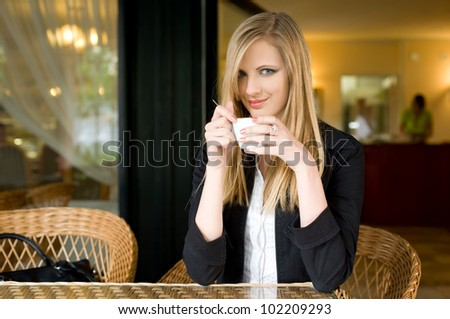 Portrait of a beautiful elegant young blond woman having coffee.