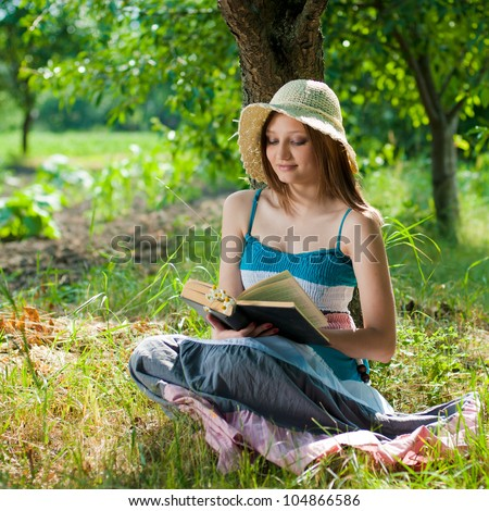 Portrait of a beautiful elegant young woman sitting outdoors barefoot and reading a book in the park or garden on a bright sunny day of summer on the green grass background
