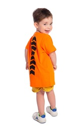 Portrait of a beautiful European boy 2 years old in full growth, rear view. A beautiful and happy child. A child's smile. Isolated on a white background in an orange t-shirt.