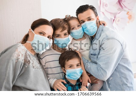 Portrait of a beautiful family at home during a Corona virus pandemic. They all wearing facemask