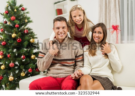 Portrait of a beautiful family of three is gathered together by a Christmas tree. Looking at camera.