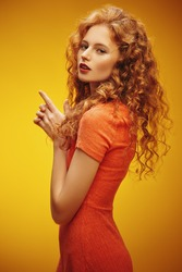 Portrait of a beautiful fashion girl with magnificent long red hair over yellow background. Beauty, fashion.