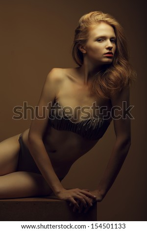 Portrait of a beautiful fashion red-haired model in stylish underwear posing over beige background. Vogue style. Studio shot