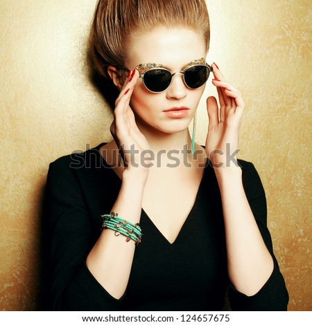 Portrait of a beautiful fashion red-haired model with a great makeup of golden foil posing over golden background and holding vintage sunglasses. studio shot