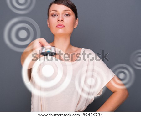 Portrait of a beautiful fashionable elegant woman with remote control choosing channels. Copyspace