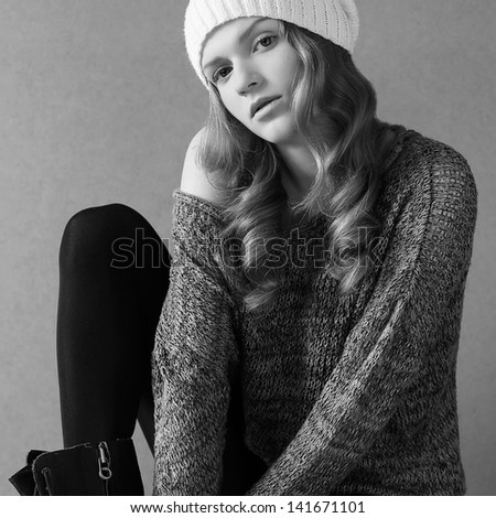 Portrait of a beautiful fashionable model with long curly hair in white hat posing over gray background. Studio shot. Daylight