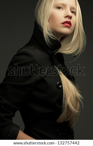 Portrait of a beautiful fashionable model with natural blond hair and great make-up in trendy black coat posing over dark gray background. Studio shot