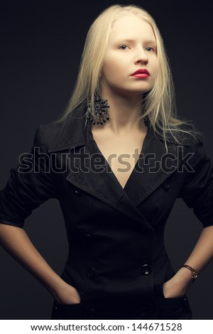 Portrait of a beautiful fashionable model with natural blond hair and great make-up in trendy black coat posing over dark gray background. Hands in pockets. Studio shot