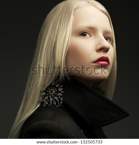 Portrait of a beautiful fashionable model with natural blond hair and great make-up posing over dark gray background. Close up. Studio shot