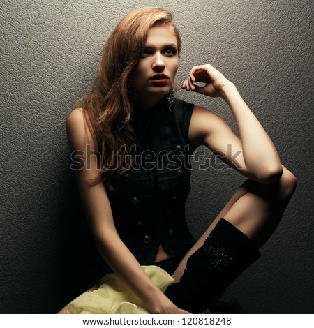 Portrait of a beautiful fashionable red-haired (ginger) model posing over gray background. Studio shot
