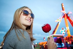 Portrait of a beautiful fashionable young woman in an amusement park arcade ground wearing sunglasses with reflections of rides and lights, holding a red caramel apple during evening night time.