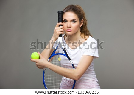 portrait of a beautiful female athletes with a tennis racket and the tennis ball in his hands