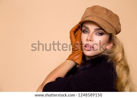 Portrait of a beautiful female model in a autumn-winter clothing, beret and leather gloves on a beige background in the studio