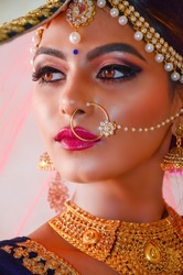 Portrait of a beautiful female model in traditional ethnic Indian bride costume with heavy jewellery and makeup
