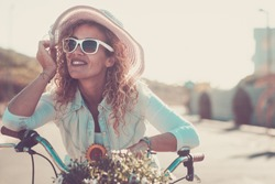Portrait of a beautiful female with curly hair riding an old bicycle. Happy middle aged people enjoying nature and healthy lifestyle.