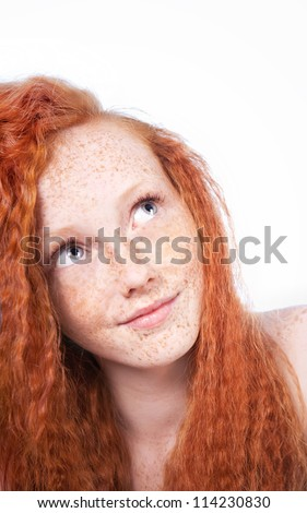 Portrait of a beautiful freckled young woman looking up, isolated on white