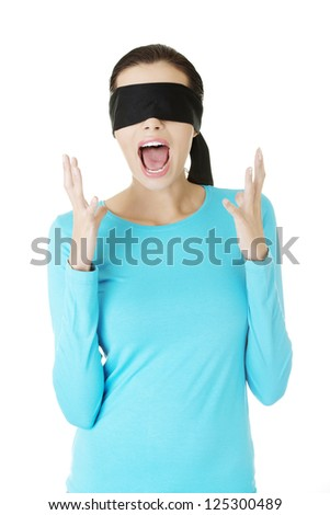 Portrait of a beautiful frighten young blindfold woman screaming in panic