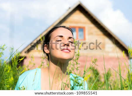 Portrait of a beautiful girl against a wooden house