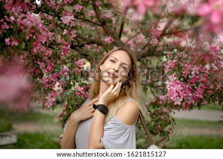Portrait of a beautiful girl among spring foliage and pink flowers of apple wearing fashion summer grey sundress. wears fitness tracker health bracelet on hand