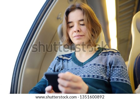 Portrait of a beautiful girl communicating on the phone in a train car. Mobile communication - the joy of communication from everywhere. Modern technologys. #1351600892