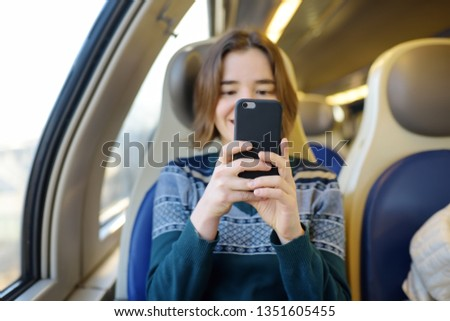 Portrait of a beautiful girl communicating on the phone in a train car. Mobile communication - the joy of communication from everywhere. Modern technologys. #1351605455