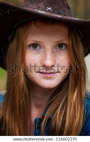 portrait of a beautiful girl-cowboy with freckles, close-up