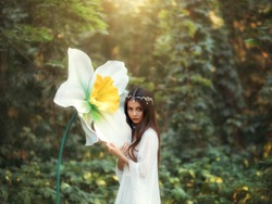 Portrait of a beautiful girl elf with long hair stands in a fantasy forest and hugs a huge daffodil flower, green trees. A woman in a white vintage dress and a silver diadem. Innocent attractive face.