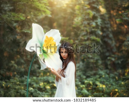 Portrait of a beautiful girl elf with long hair stands in a fantasy forest and hugs a huge daffodil flower, green trees. A woman in a white vintage dress and a silver diadem. Innocent attractive face. Stock photo ©