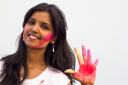 Portrait of a beautiful girl full of colored powder all over the body. Young girl plays with colors on the occasion of Holi. Concept for Indian festival Holi. Blank space available for written text.