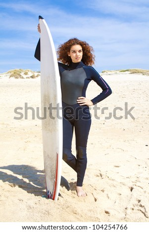 Portrait of a beautiful girl holding a surf board