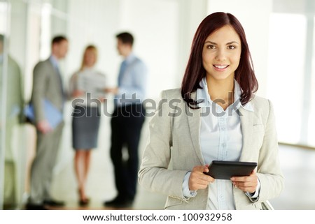 Portrait of a beautiful girl holding a tablet computer and looking at camera