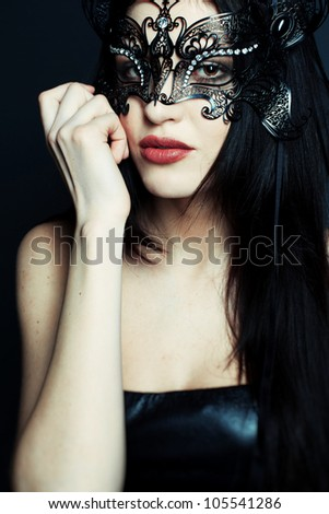 Portrait of a beautiful girl in a black dress with a theatrical mask on her face